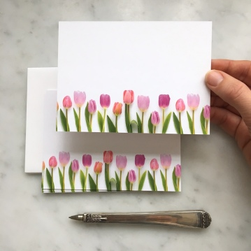 row of tulips flat ard by bottle branch small